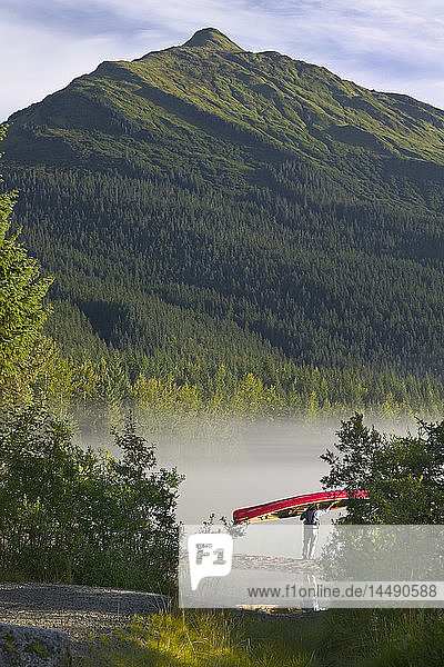 Person Carries Canoe to Mendenhall Lake SE AK Summer Tongass NF Morning