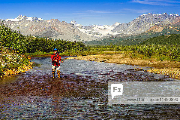 Man fly fishing in Gunn Creek off the Richardson Highway with Gulkana Glacier and the Alaska Range in the background  Interior Alaska  Summer