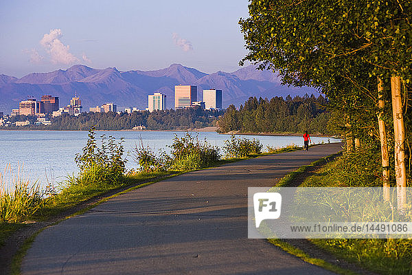 People jogging  walking and biking on the Tony Knowles Coastal Trail with Downtown Anchorage skyline in the distance  Anchorage  Southcentral Alaska  Summer