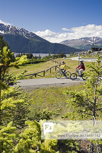 Young Couple Bikes on Path @ Bird Pt Rest Stop AK SC Turnagain Arm Chugach Mtns Summer