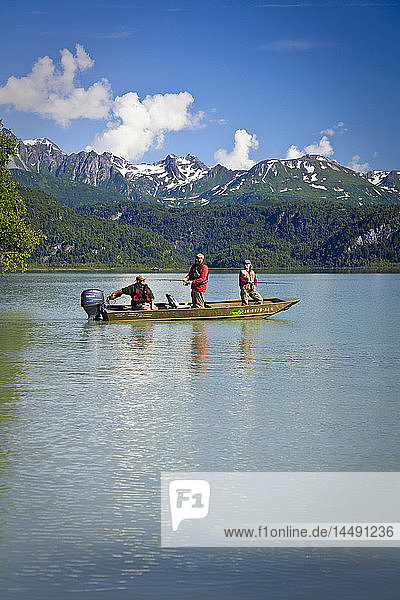 Man and Woman spin fish while standing in a boat in Big River Lakes in the Redoubt Bay State Critical Habitat Area in Southcentral Alaska during Summer
