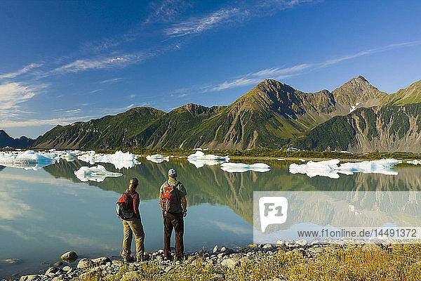 Couple hiking along the shore of Bear Glacier Lake in Kenai Fjords National Park  Kenai Peninsula  Southcentral Alaska  Summer