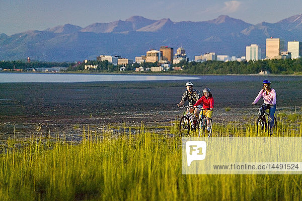 Family riding bicycles on beach next to Tony Knowles Coastal Trail Anchorage Alaska Summer
