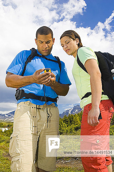 Couple hiking and geocaching with GPS and map on trail below Flat Top Mountain  Glenn Alps area  Southcentral Alaska