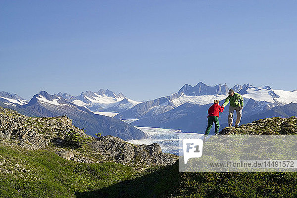 Couple hiking on ridge Coast Mtns w/Mendenhall Glacier Tongass National Forest Southeast Alaska