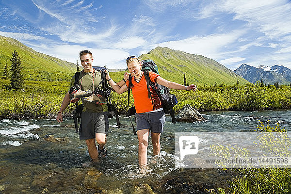 Hikers in Chugach State Park crossing South Fork of Eagle River using correct fording techniques Alaska