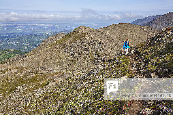 Woman hiking on McHugh Peak trail in Chugach State Park with Anchorage  Alaska in background