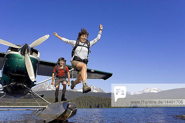 People leap from floatplane to shoreline on lake to go hiking Kenai Mtns Kenai Peninsula Alaska Summer