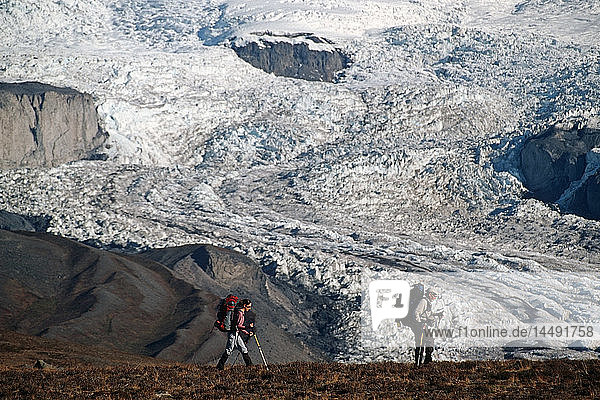Pair of backpackers hike across a plateau with Mount Wrangell looming in the background ar Wrangell-St.Elias National Park in South Central Alaska. Fall