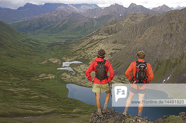 Two hikers view alpine lake during run through the Chugach Mountains a rugged 32-mile link-up of Chugach front range peaks Southcentral Alaska summer