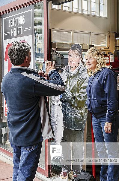 Man photographing woman standing next to life-size cut out of Sarah Palin holding a salmon  Juneau  Southeast Alaska