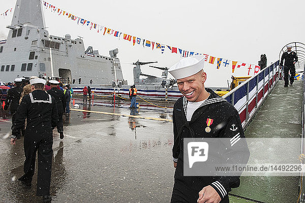 Navy crew members at the commissioning ceremony for the USS Anchorage in its namesake port on a snowy day in May.