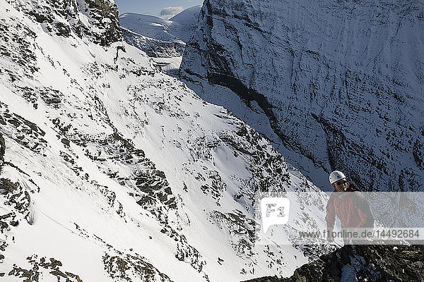 Man climbing up snowcapped Kebnekaise mountain