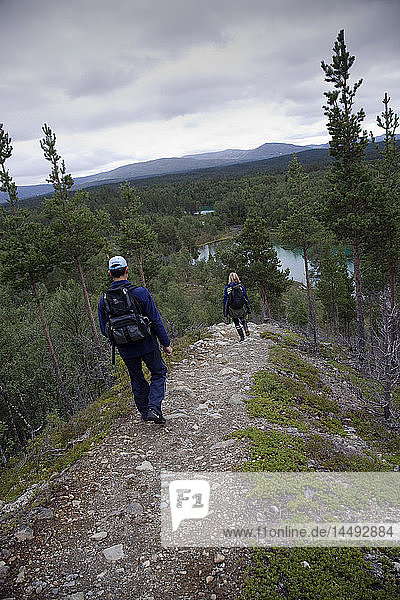Two hikers hiking on mountains