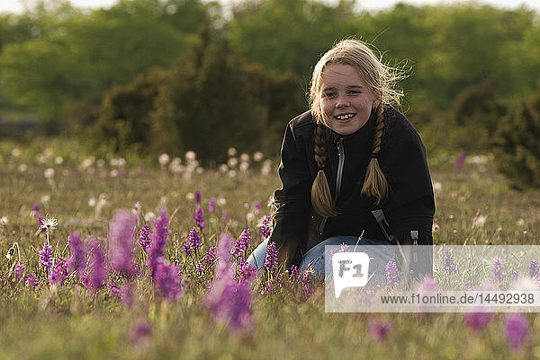 Girl on meadow looking at camera and smiling