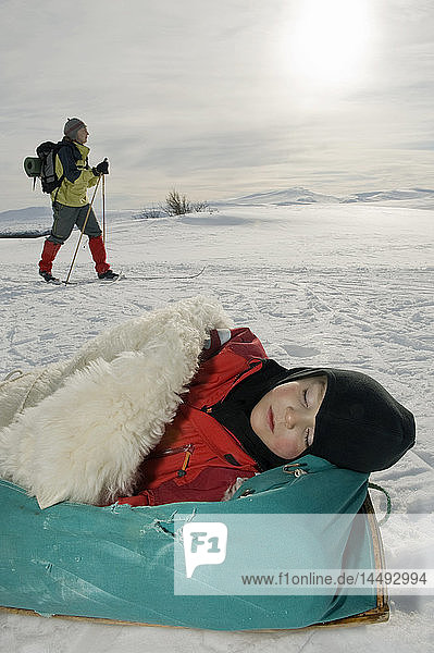 Boy sleeping on sleeping bag with woman walking in the background