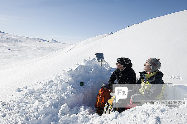 Couple resting on snow covered hill