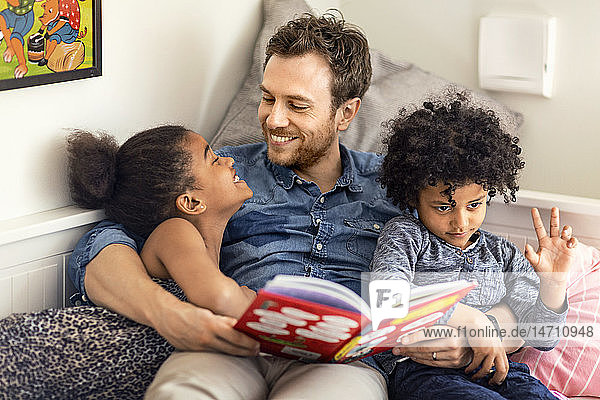 Father reading book to children