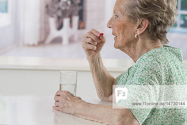 Senior woman taking a medicine.