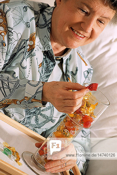 ELDERLY PERSON EATING SWEETS