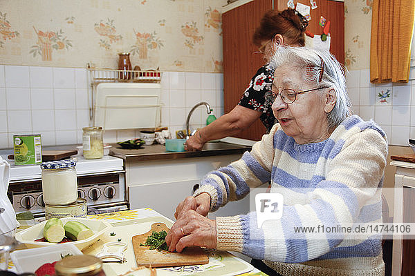 An elderly woman cooking in her home  helped by her daughter who is her guardian.