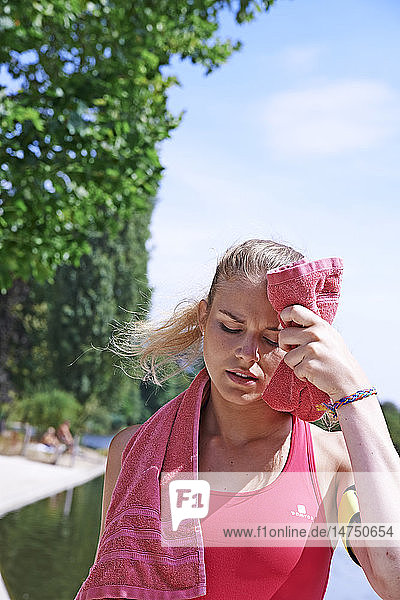 Woman wiping her face after exercising.