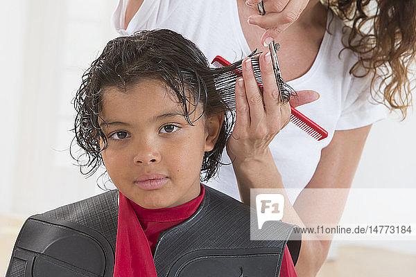 Hairdresser cutting boy´s hair.