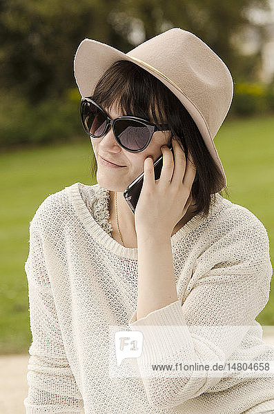 Young woman telephoning in a park.