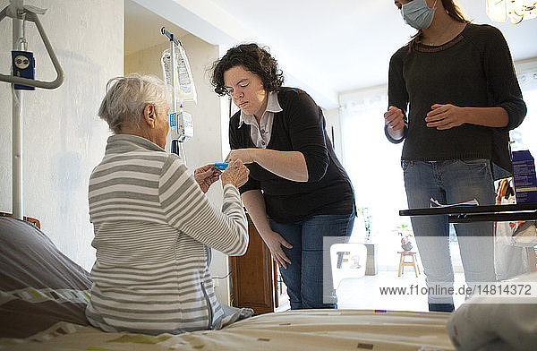 Reportage on a home health care service in Savoie  France. An auxiliary nurse gives a patient a tablet container box.