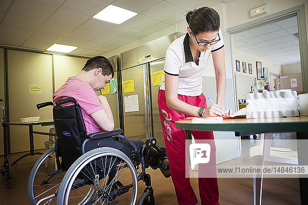 Reportage on a sports instructor specialising in adapted physical activity in a specialised care home for adults with mutliple disabilities in France. The instructor notes down the physical progress of the young man. The Science and Technique of Physical