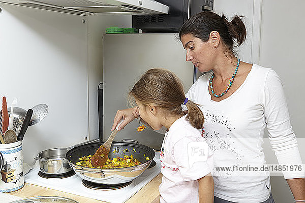 Mother and daughter cooking.