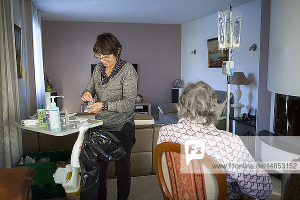 Reportage on a home health care service in Savoie  France. A nurse changes a patient with cancer's parenteral nutrition pouch.