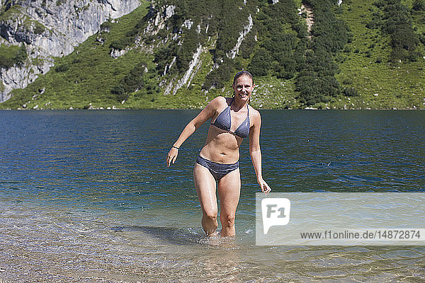 Young woman wading in mountain lake