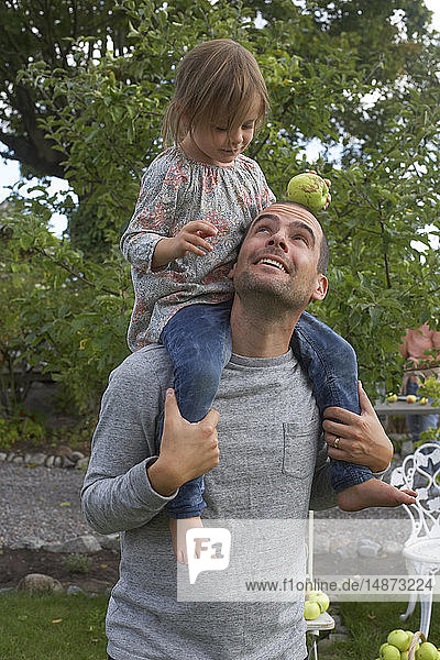 Man carrying daughter on shoulders