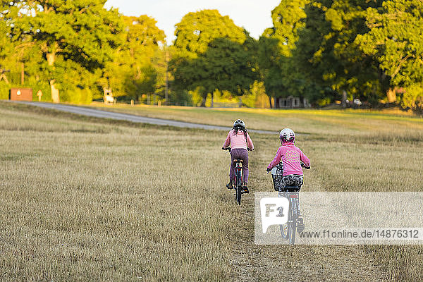 Girls on bicycles in meadow