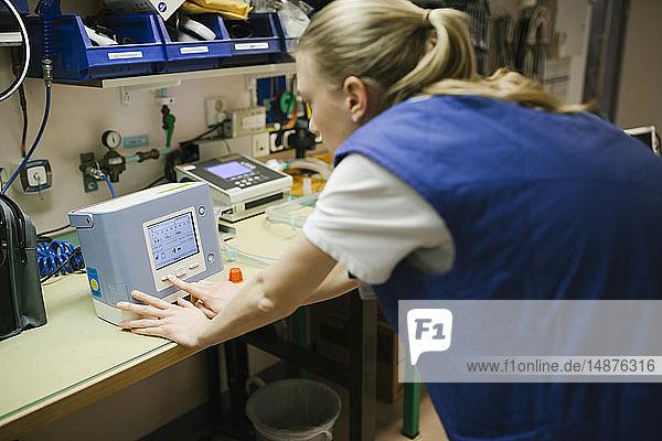 Female engineer checking hospital equipment
