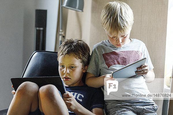 Boys using digital tablets