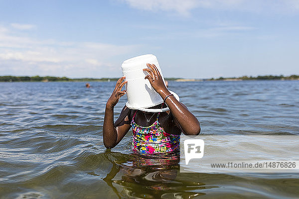 Girl in sea with bucket on her head