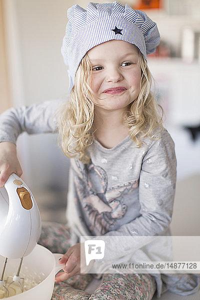 Girl using electric mixer