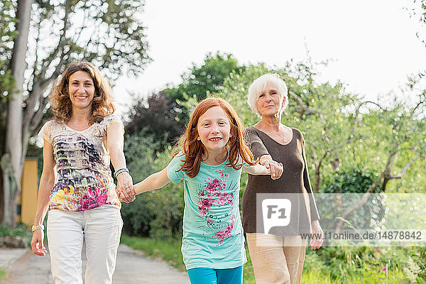 Girl on rural road holding hands with mother and grandmother  portrait
