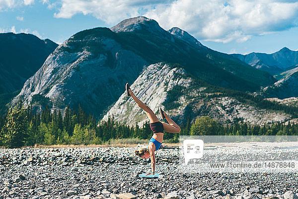 Frau macht Handstand auf einem Steinfeld  Jasper  Kanada