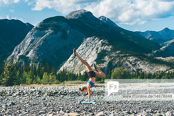 Woman doing handstand on field of stones  Jasper  Canada