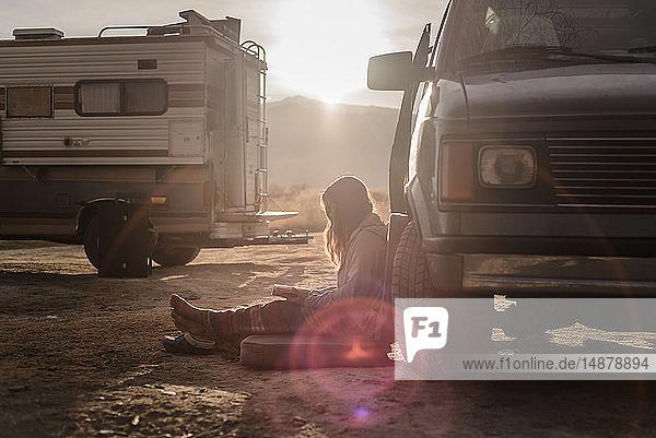 Frau liest neben einem Wohnmobil in der Wüste  Sierra Nevada  Bischof  Kalifornien  USA