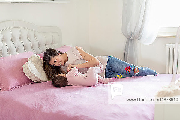 Mother playing with baby girl in bed
