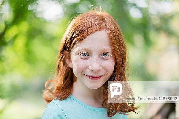 Red haired girl in garden  head and shoulder portrait