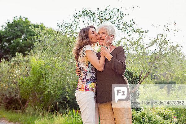 Reife Frau küsst Mutter im Garten auf die Wange