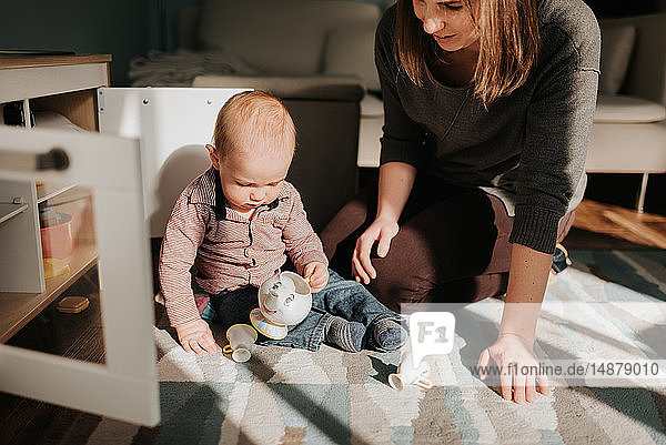 Mother playing with baby son on living room rug