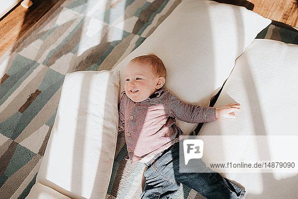 Kleiner Junge auf Kissen auf dem Wohnzimmerboden liegend  Blick von oben