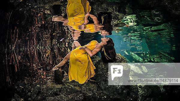 Woman in yellow gown floating underwater,  Cenote,  Quintana Roo,  Mexico