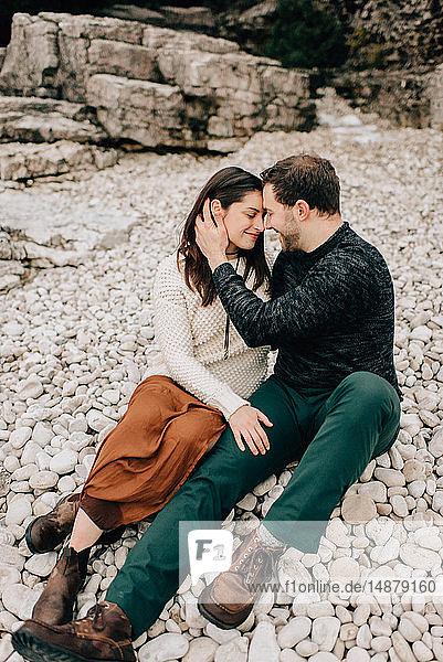Auf felsigem Boden sitzendes Ehepaar,  Tobermory,  Kanada